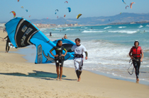 Kiter walking up the beach with instructor.